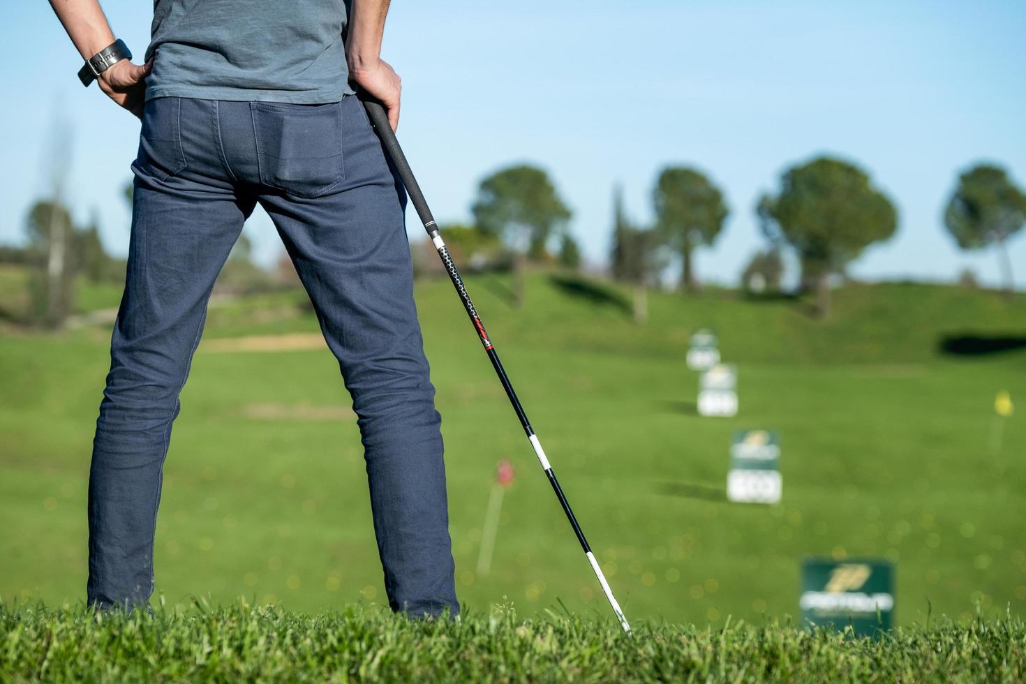 Jugador de golf con gorra recostada sobre un palo de golf mirando el curso foto