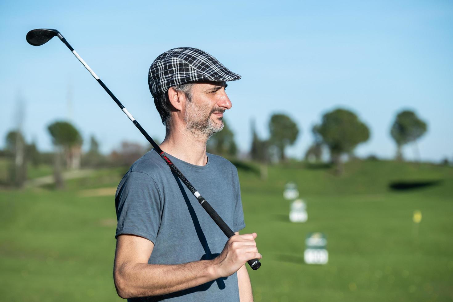 Jugador de golf con gorra y club sobre su hombro en un curso de conducción foto
