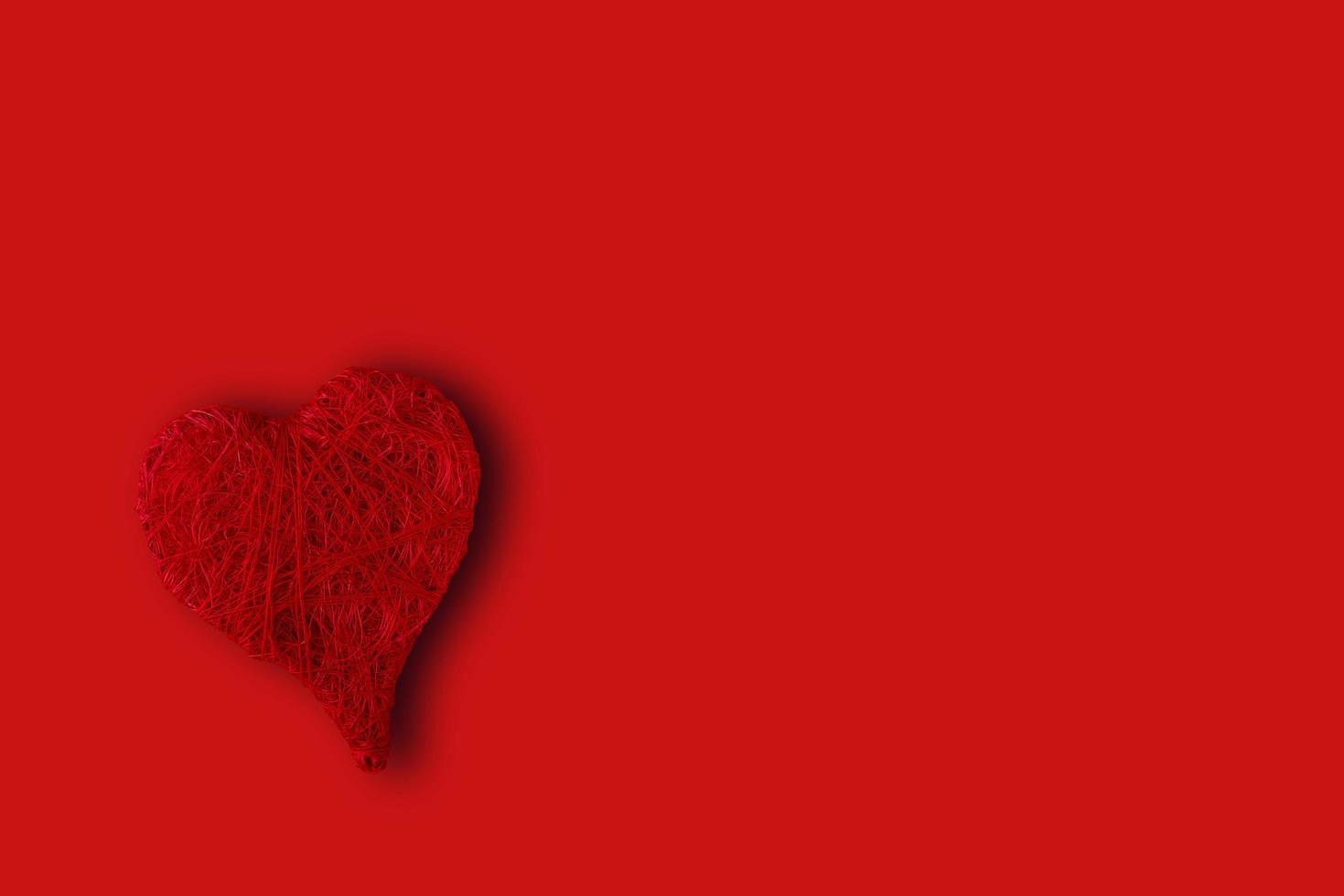 corazón rojo en la esquina inferior izquierda sobre un fondo rojo. concepto de st. día de San Valentín foto