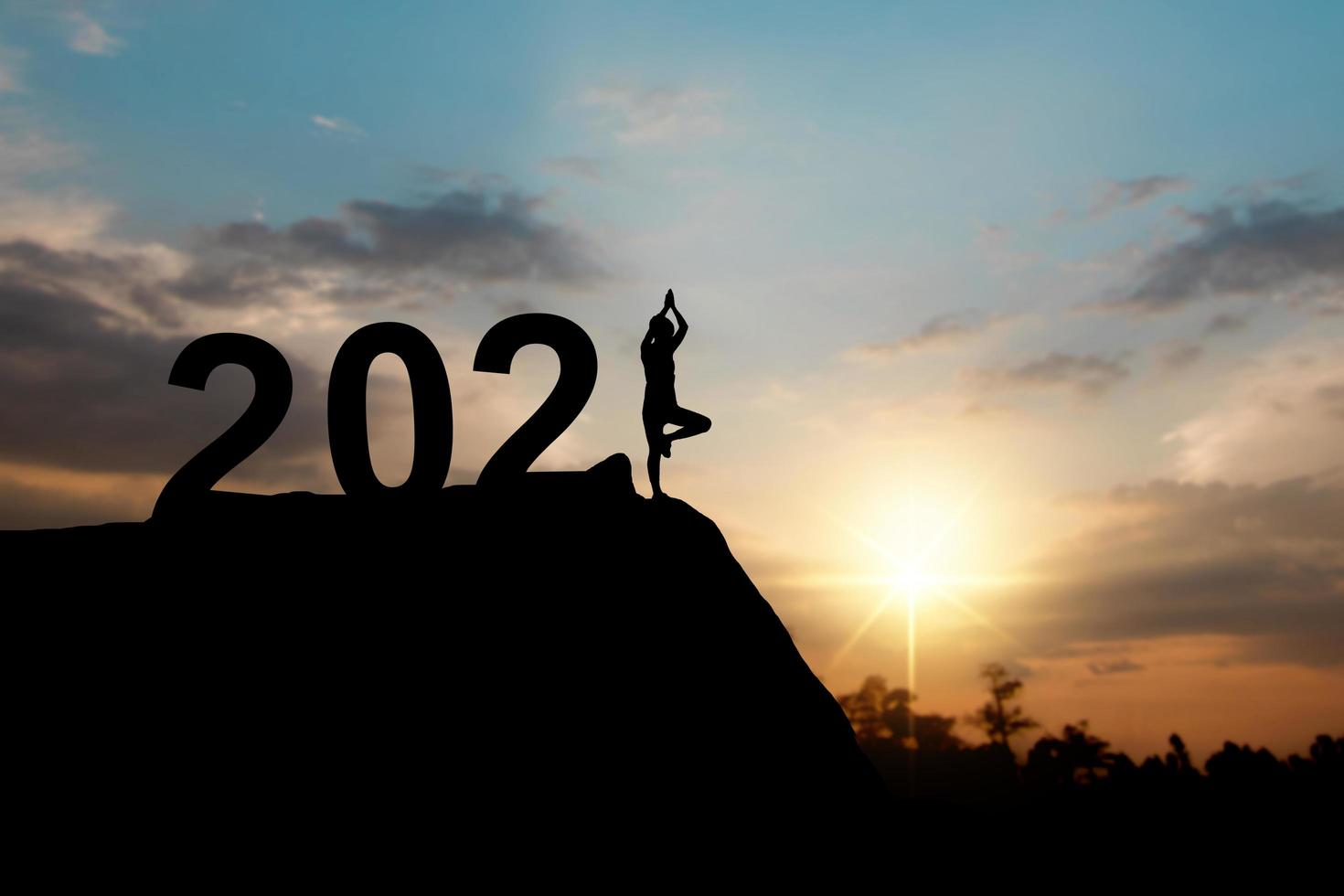 Silhouette of happy new year 2021 with woman doing yoga photo
