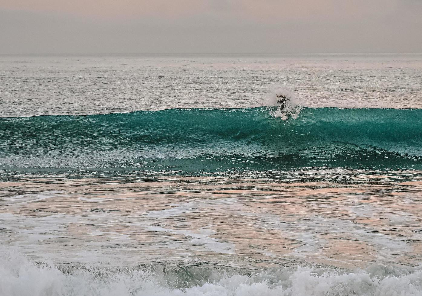 Person surfing on sea waves photo