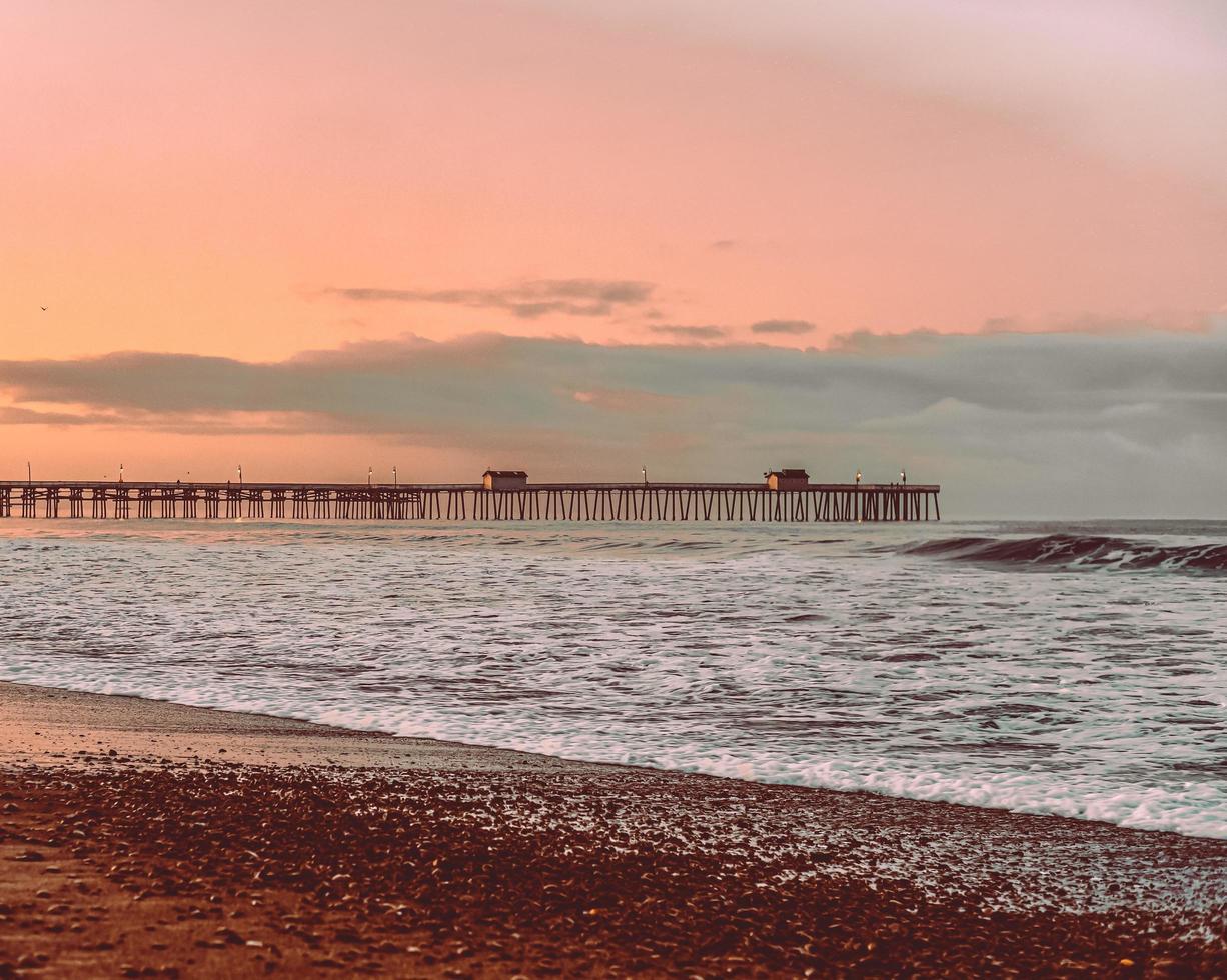 olas del mar chocando en la costa durante el atardecer foto