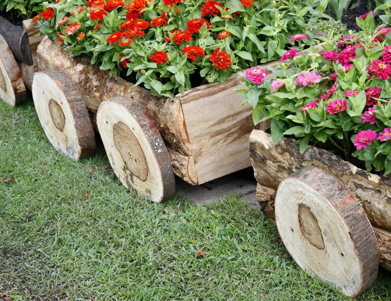 Flowers in pots in wooden box on background of garden photo