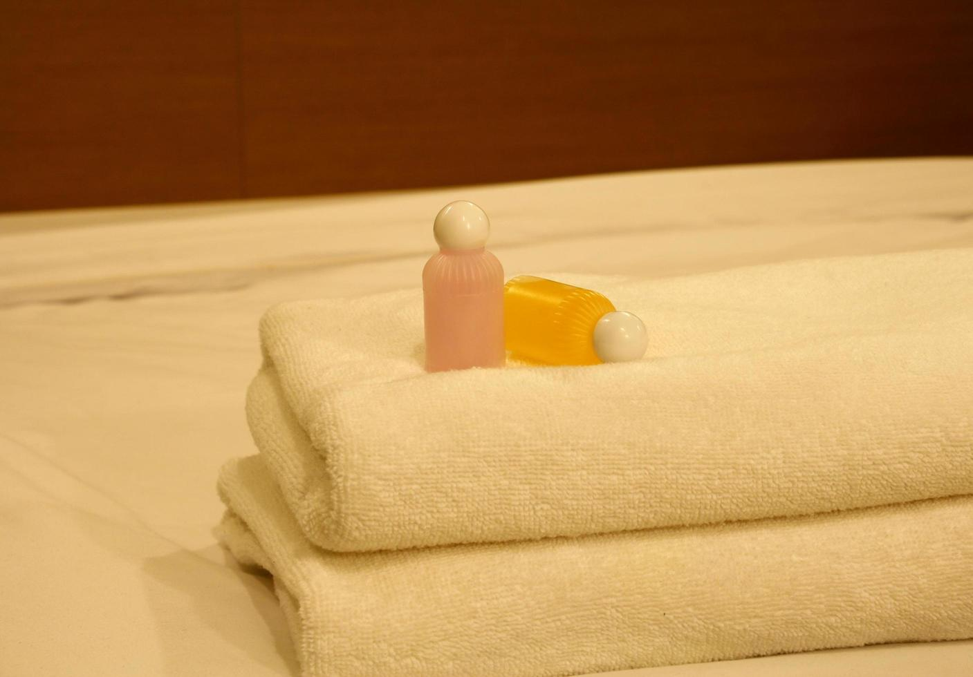 Luxurious bedroom with two towels and shampoo on the bed photo