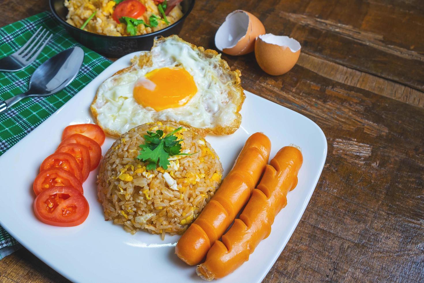 Arroz frito americano servido con huevos fritos y salchichas en la mesa foto