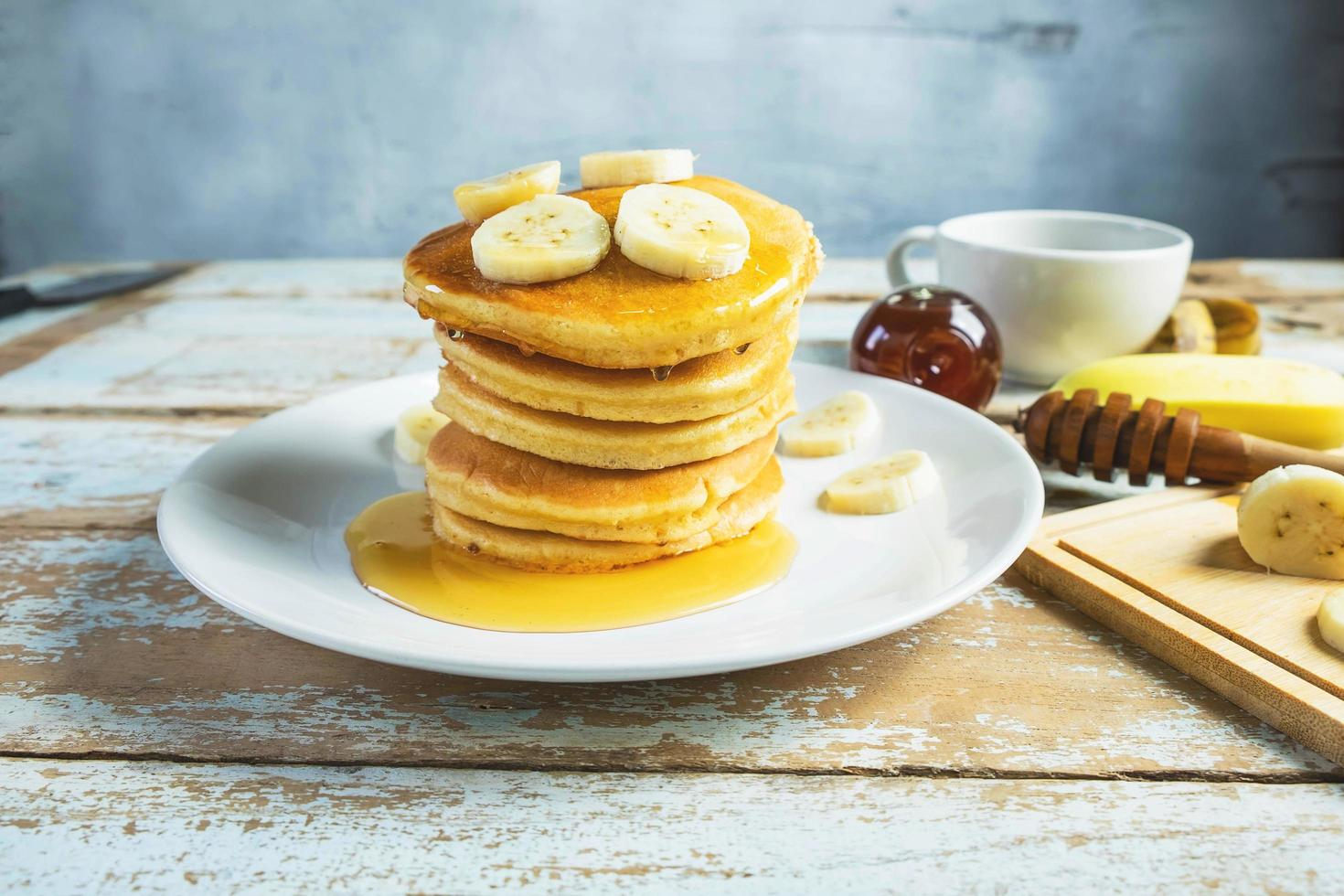 Pancakes topped with honey and bananas on the table photo