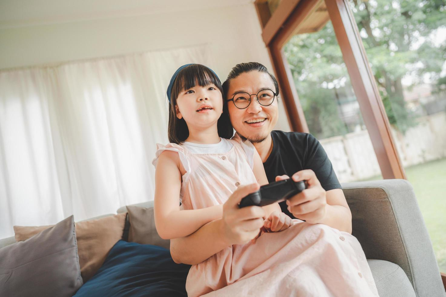Father and daughter playing video game photo