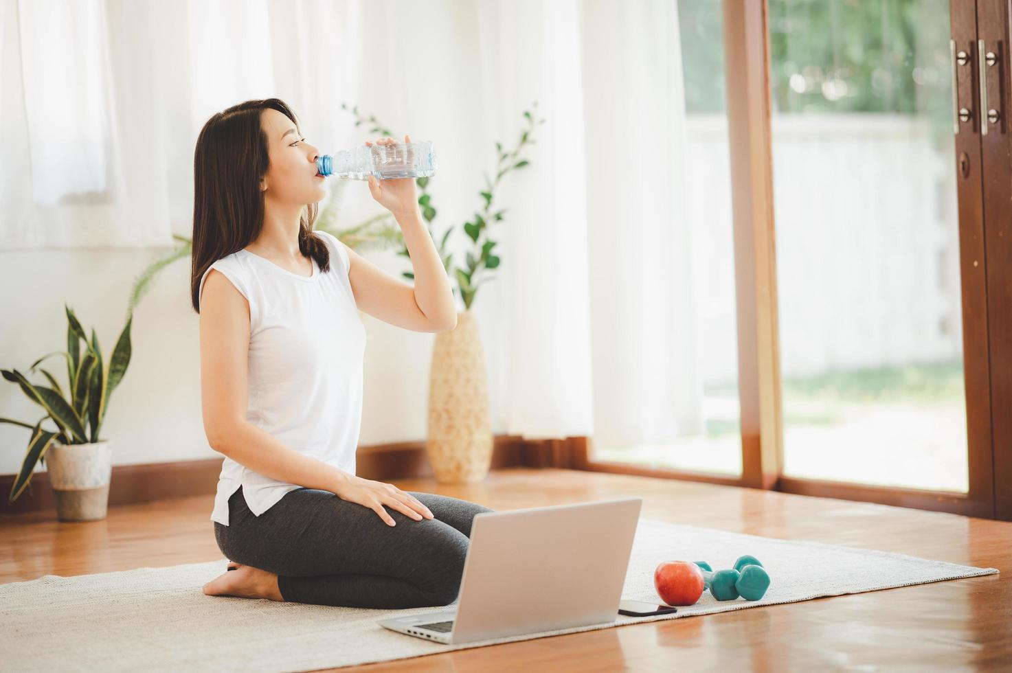 Woman drinking water while doing virtual workout photo