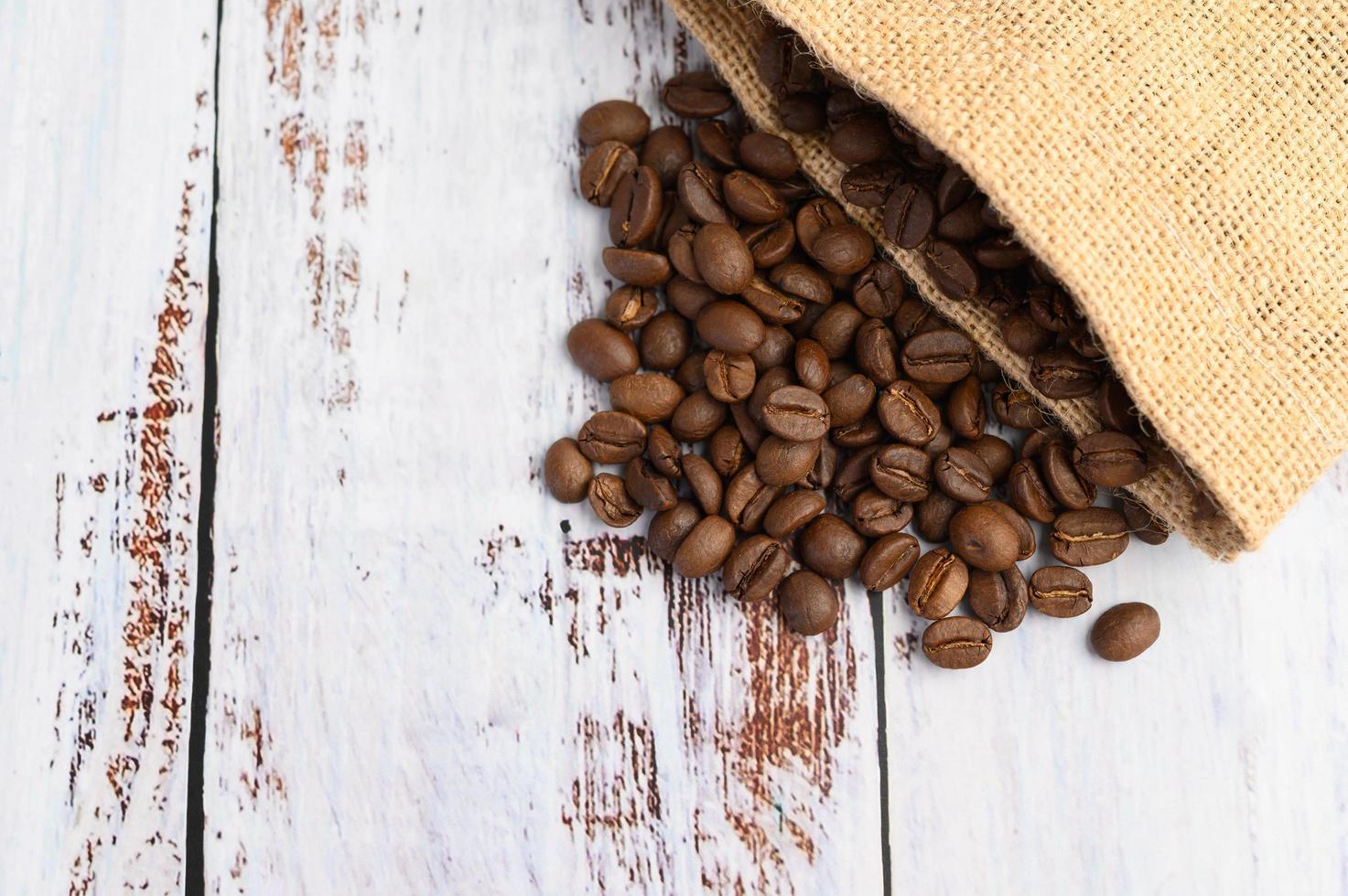 Granos de café en sacos de cáñamo sobre una mesa de madera blanca foto