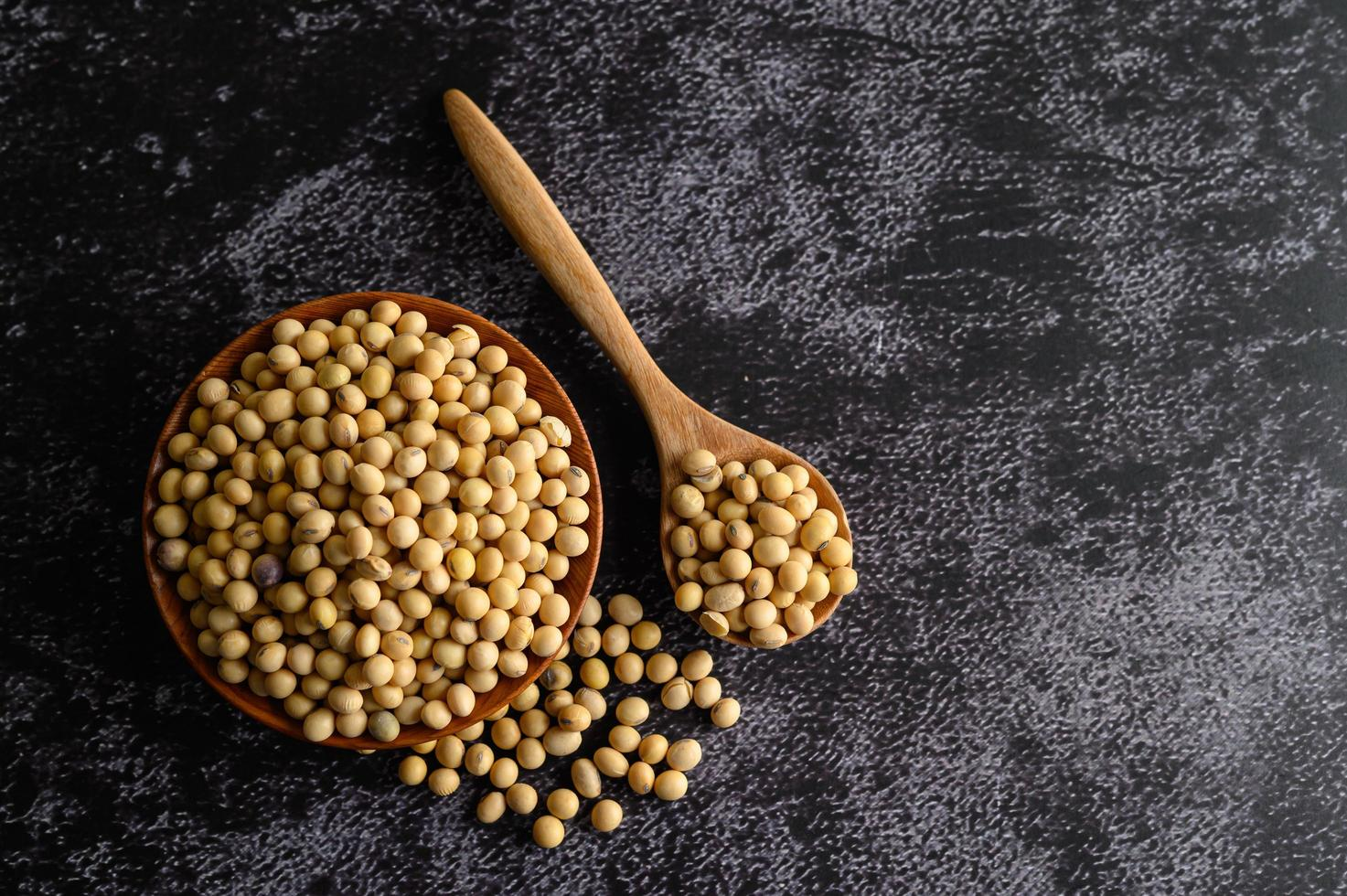 Yellow beans in a wooden bowl on black background photo
