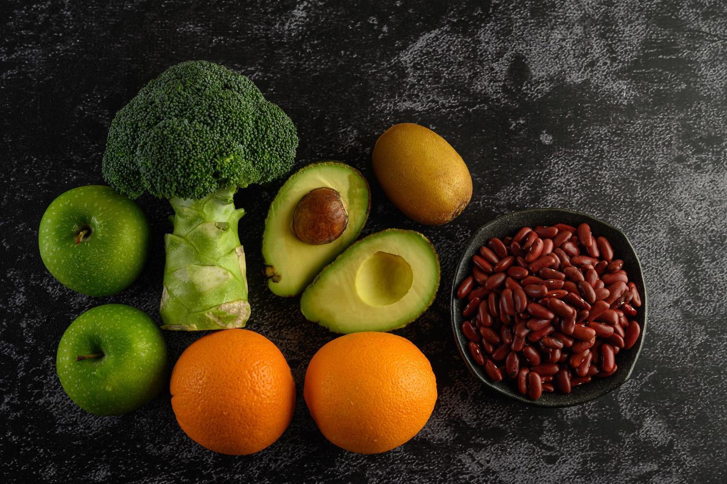 Broccoli, apple, orange, kiwi, avocado and beans on a black cement floor background photo