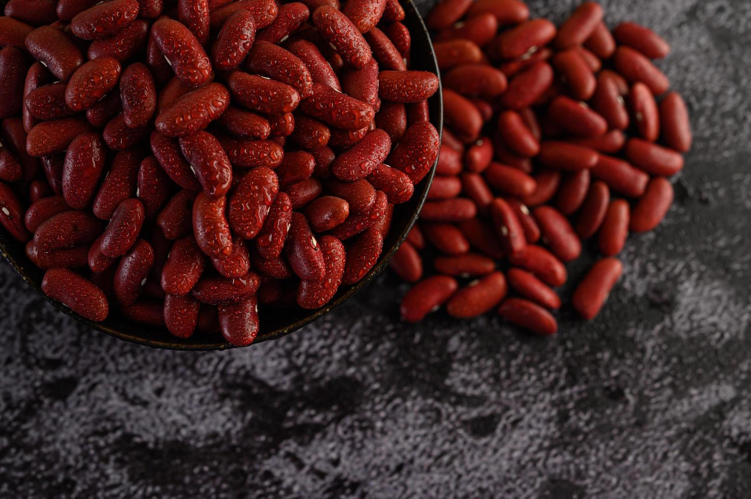 Red beans with water spray on cement background photo