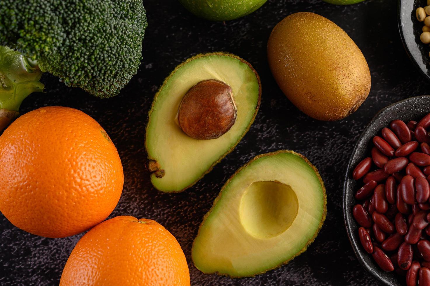 brócoli, manzana, naranja, kiwi, aguacate y frijoles sobre un fondo de piso de cemento negro foto