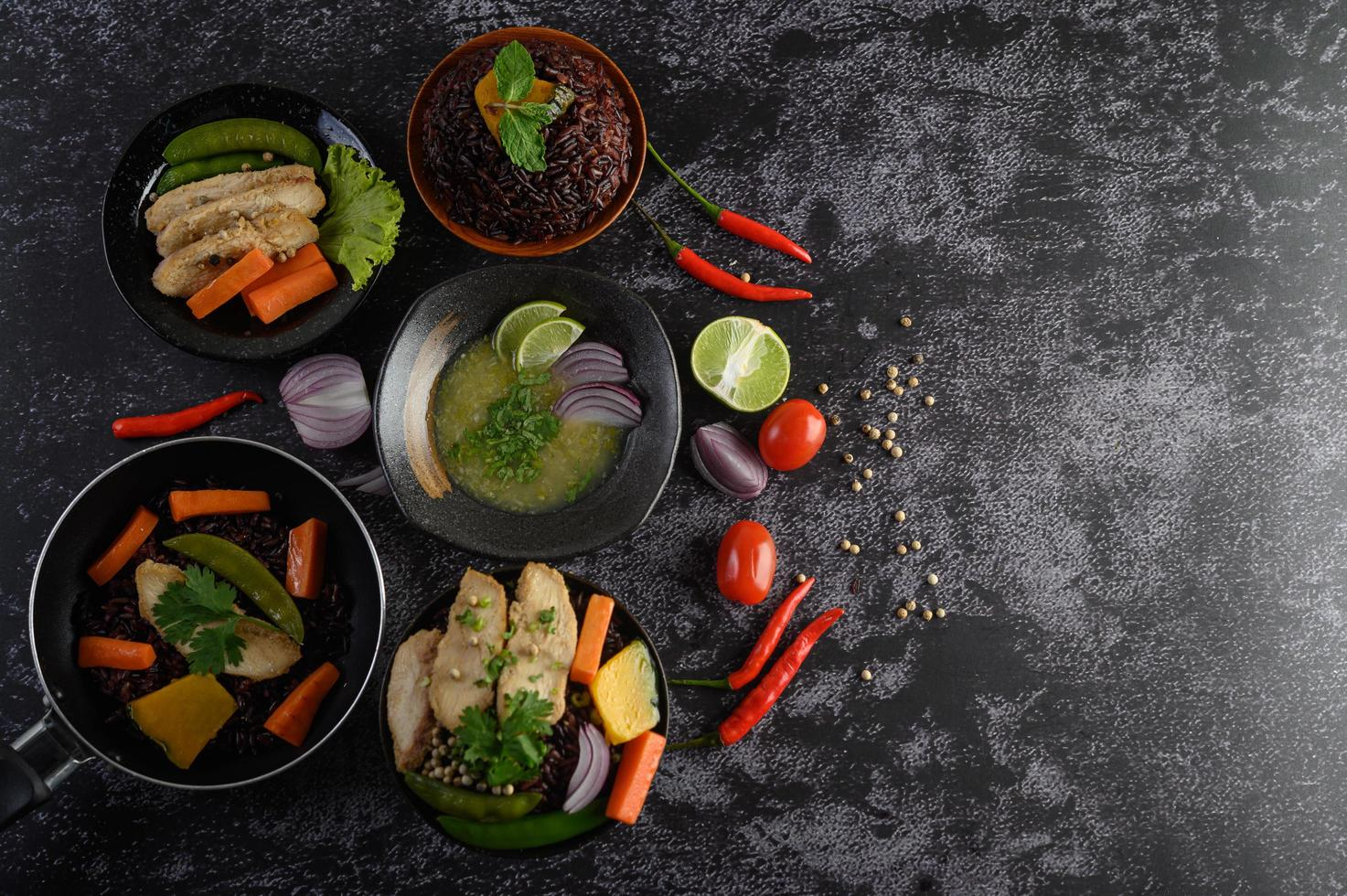 Assorted dishes of vegetables, meat and fish on a black stone background photo