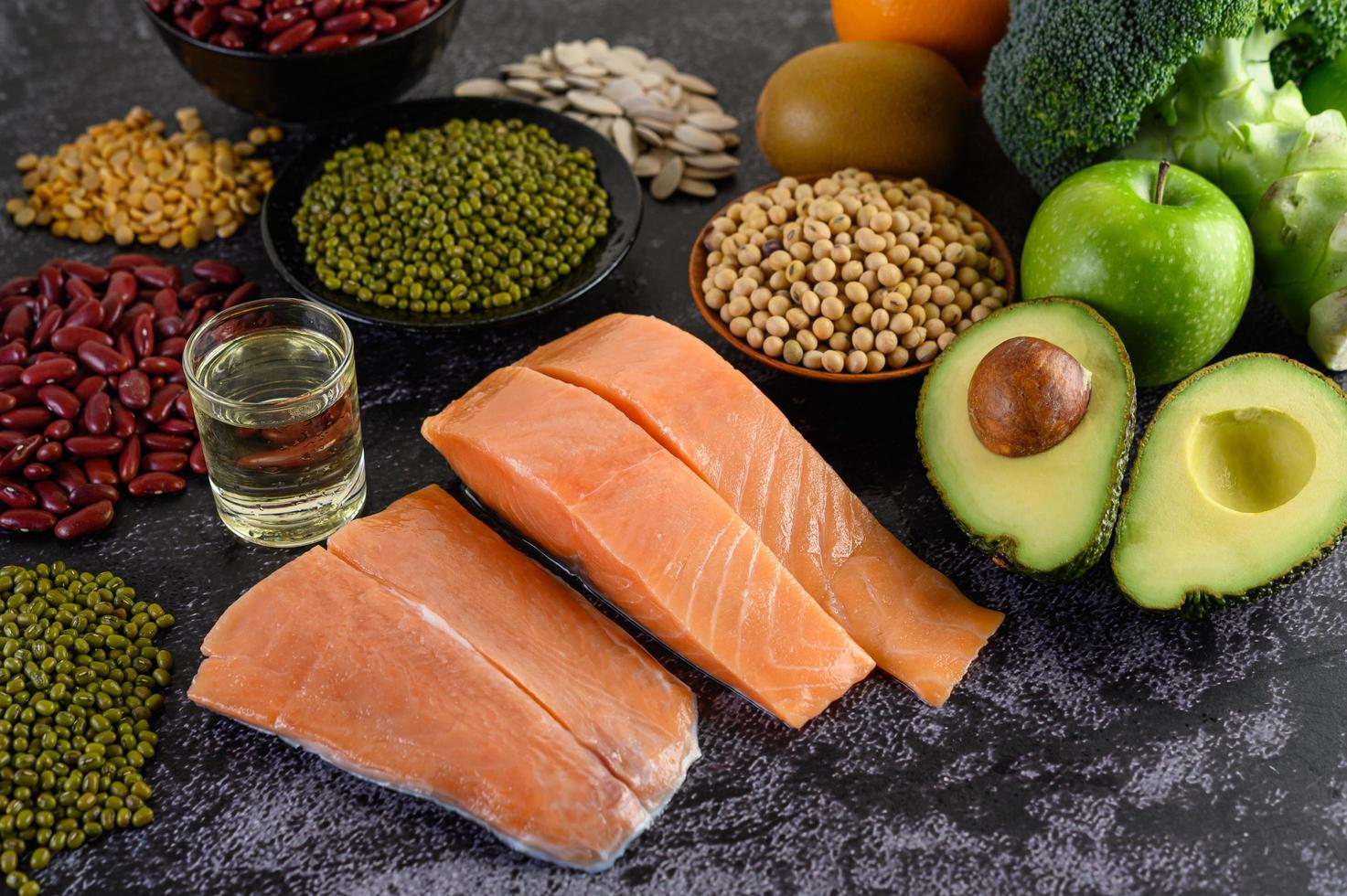 Legumes, broccoli, fruit, and salmon on a black cement background photo