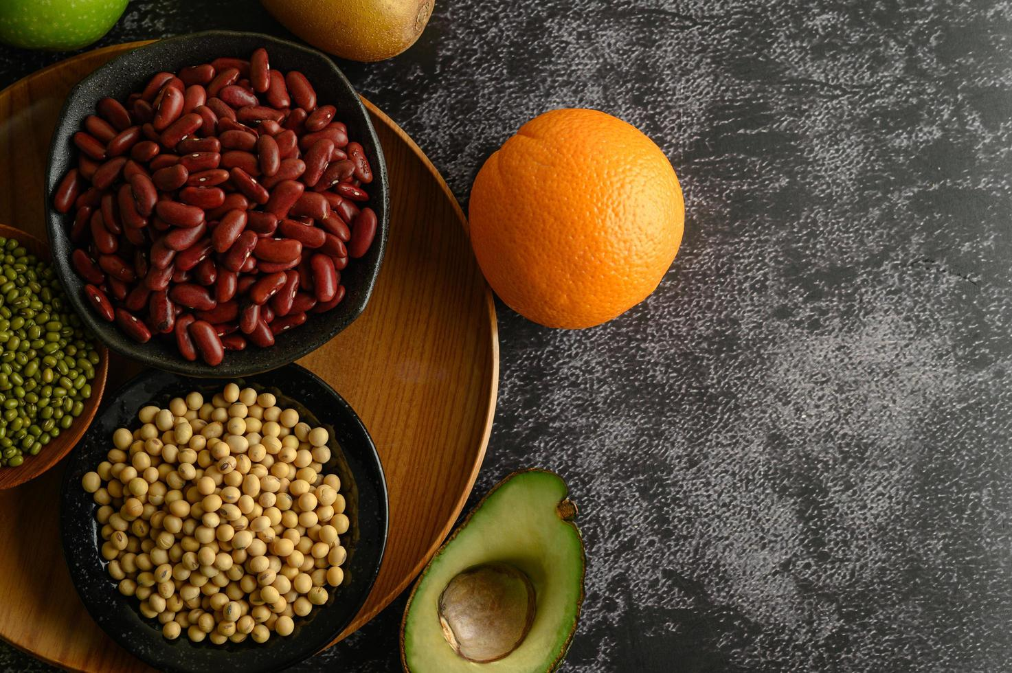 Legumes and fruit on black cement floor background photo