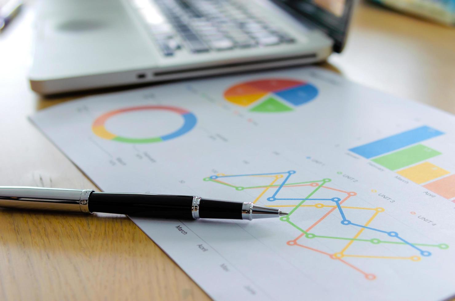 bolígrafo y gráficos en un escritorio foto