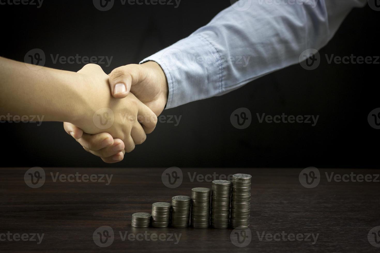 dos personas dándose la mano con una pila de monedas sobre la mesa foto