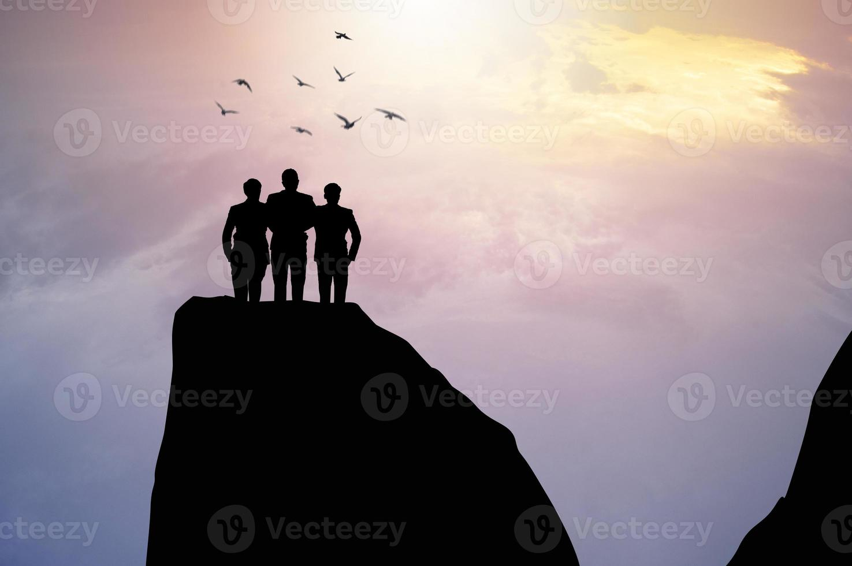 tres personas de pie en un acantilado foto