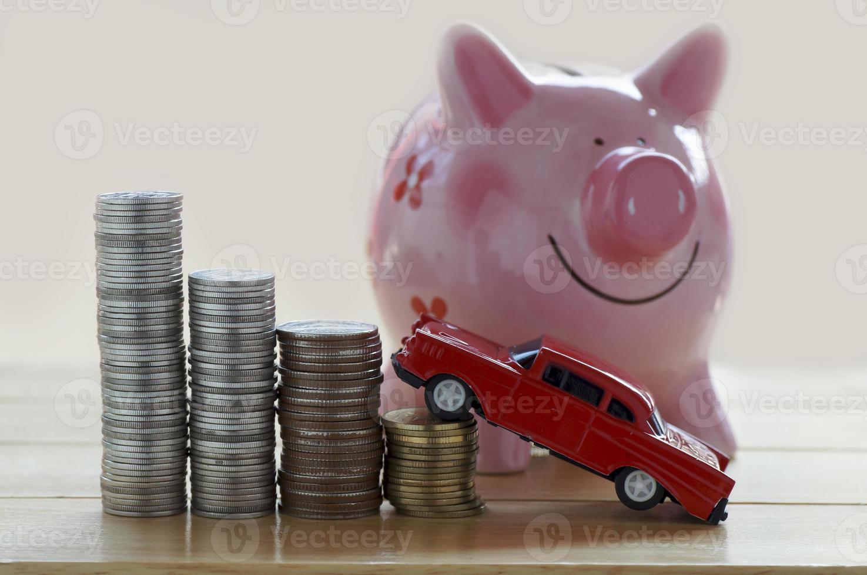 montones de monedas con coche de juguete y hucha foto