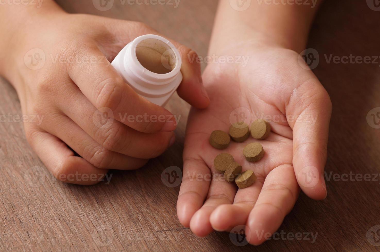 pastillas marrones en una mano foto