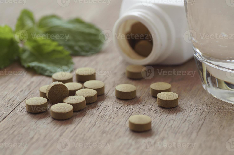 pastillas marrones con un vaso de agua foto