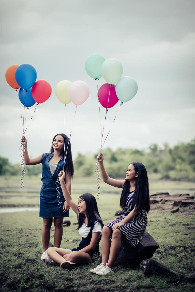 Happy group girlfriends holding multi-colored balloons at a park photo