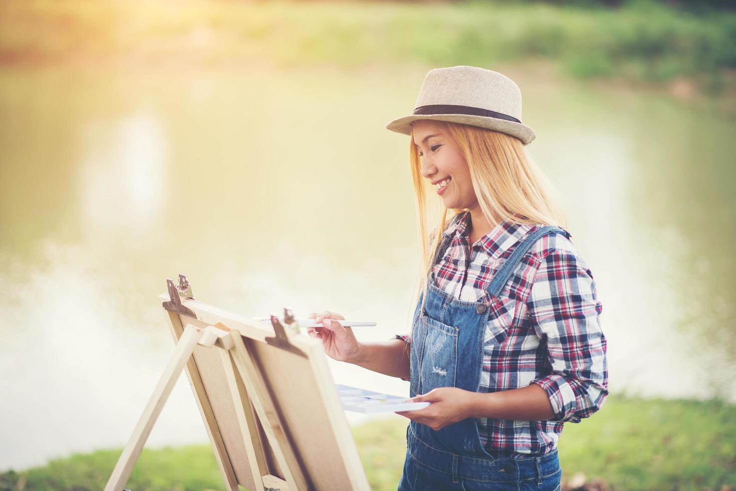 Young woman draws a picture in the park photo