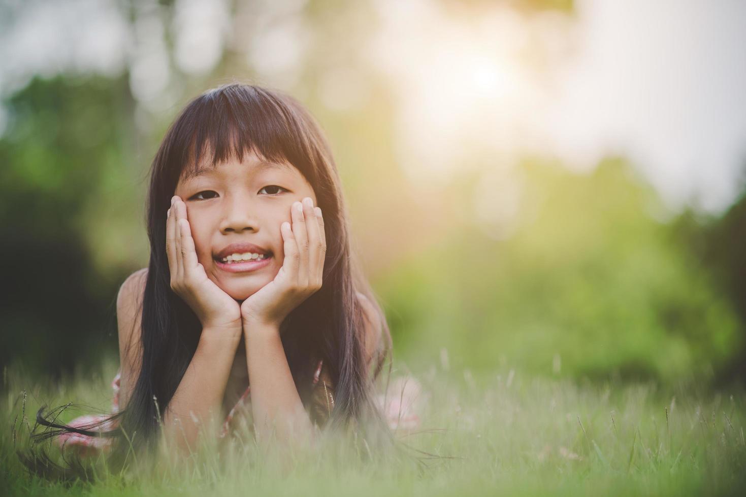 niña acostada cómodamente en la hierba y sonriendo foto
