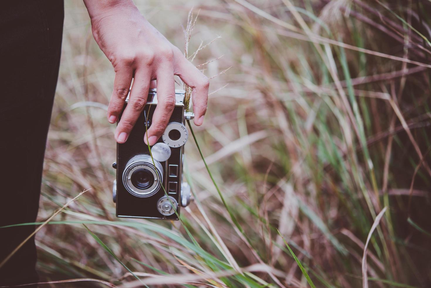 Close-up of a young woman's hand holding a retro camera in a field photo