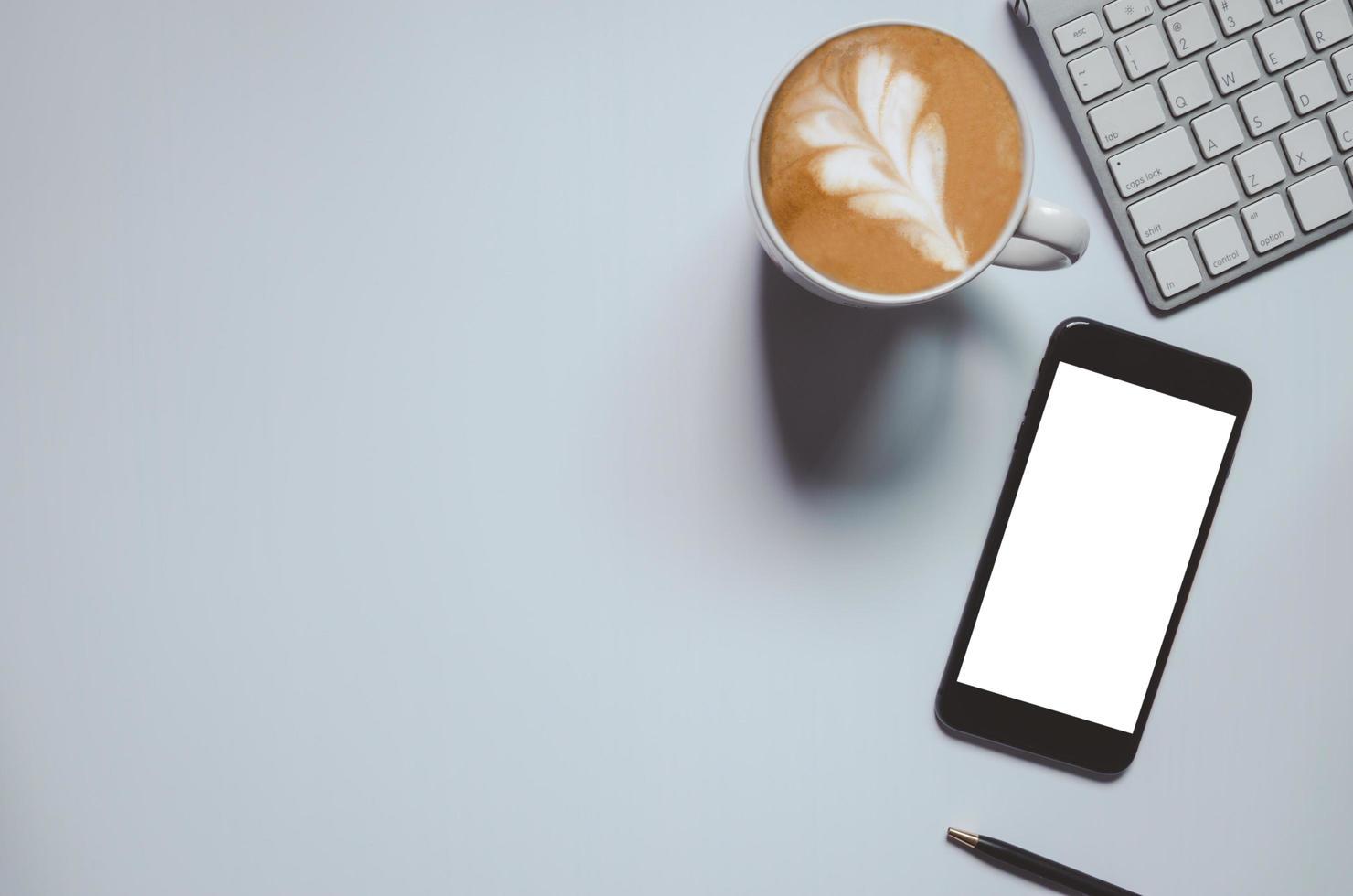 Vista superior de la maqueta de teléfono inteligente y café con leche. foto