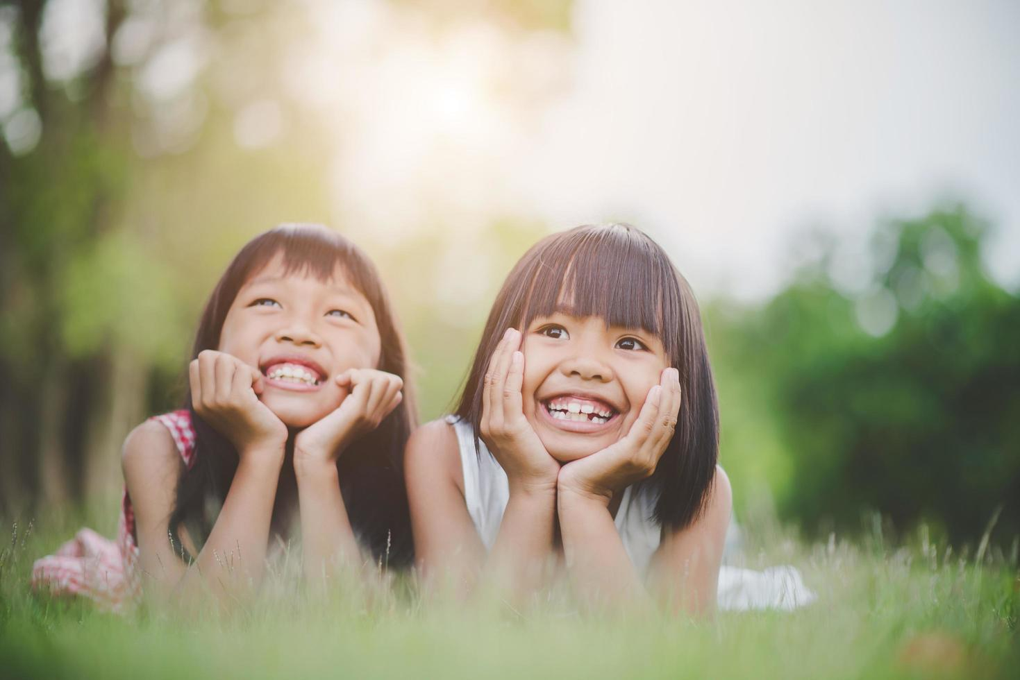 niñas recostadas cómodamente en la hierba y sonriendo foto