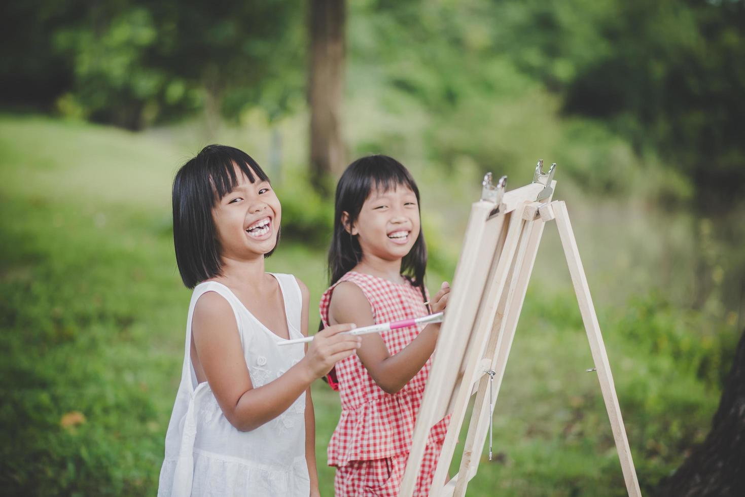 Two little girl painters drawing art in the park photo