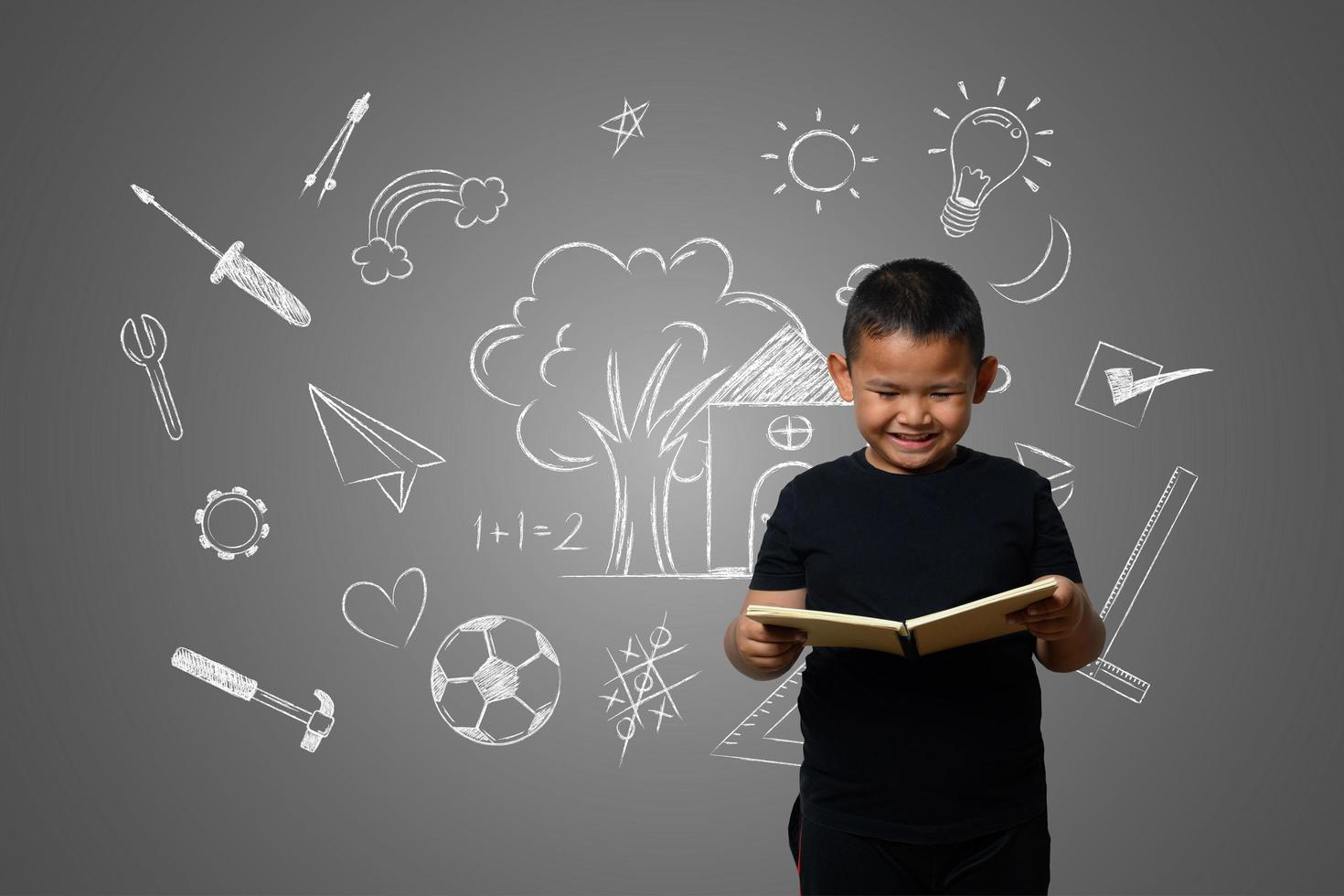 A boy and a book of knowledge on a blackboard background photo