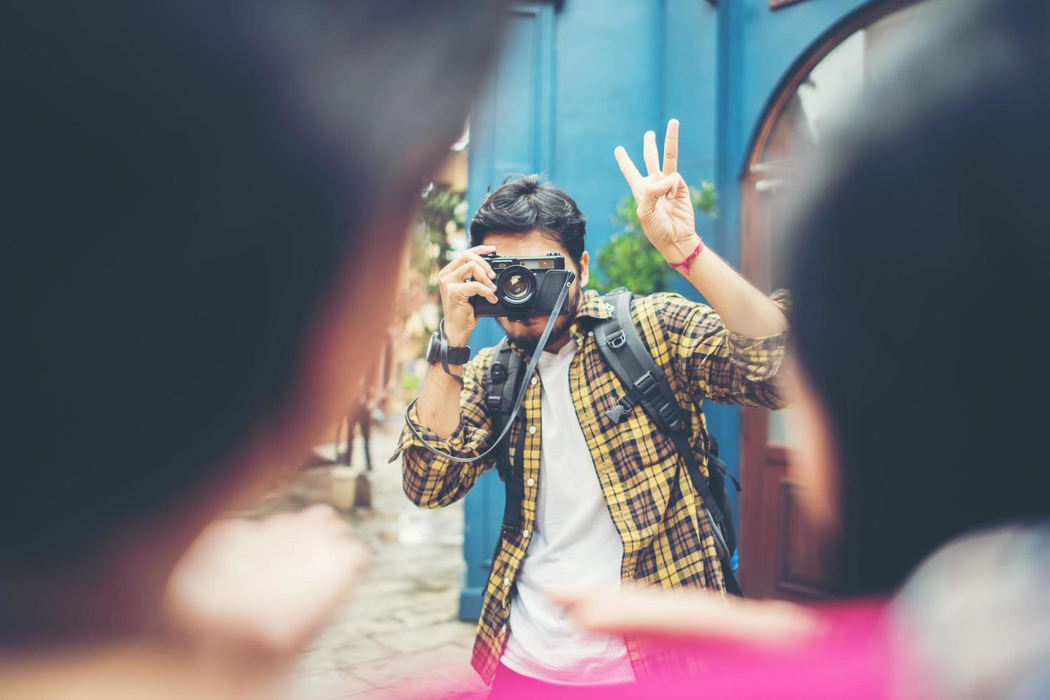 Young man taking pics of his friends while traveling in urban area together photo