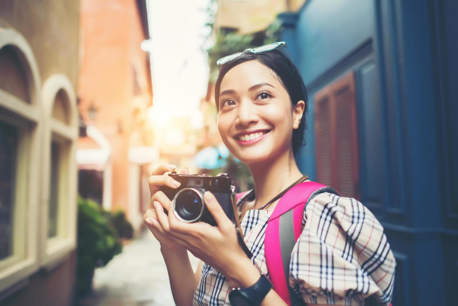 Close-up of a young hipster woman traveling and taking photos with her camera