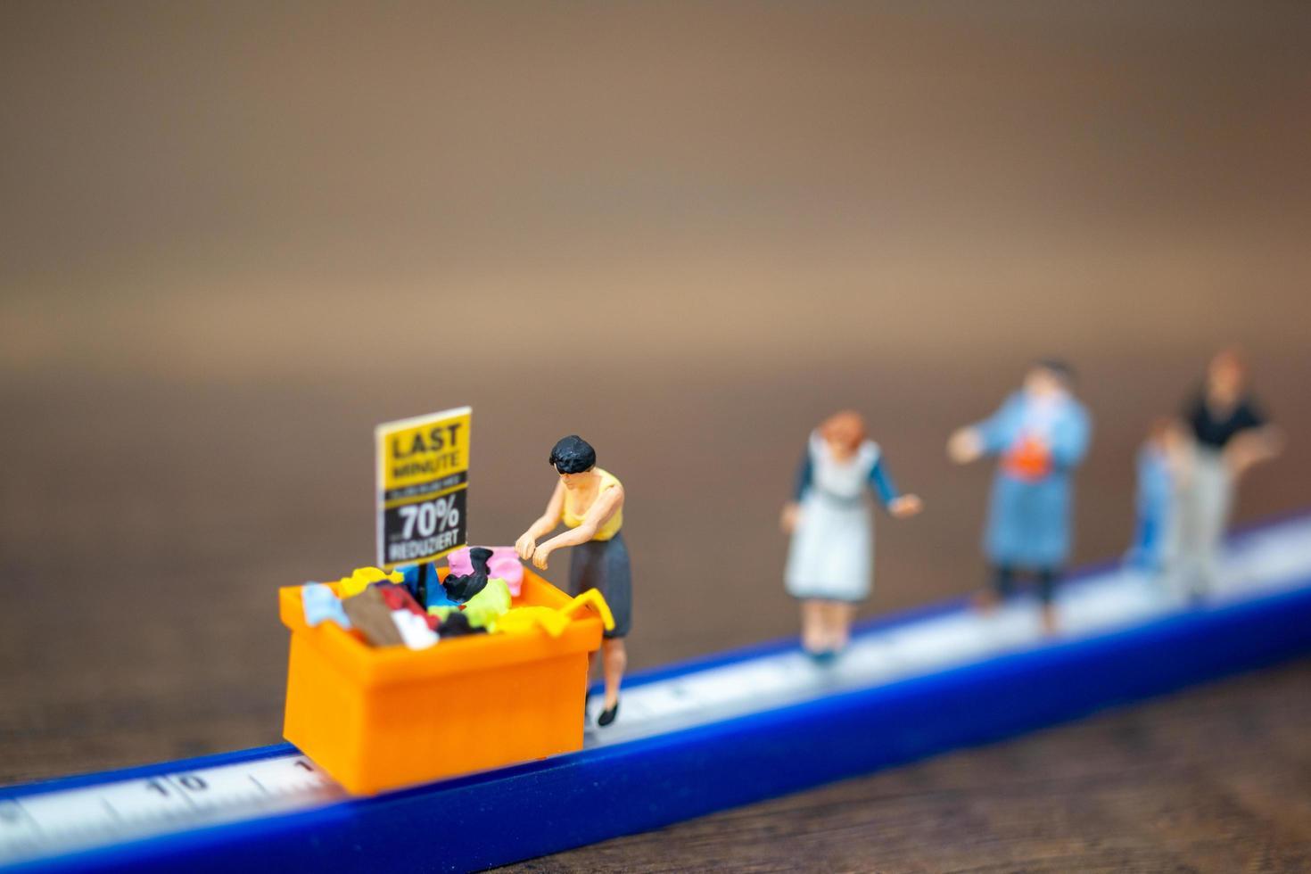 Gente en miniatura comprando en un contenedor de descuento foto