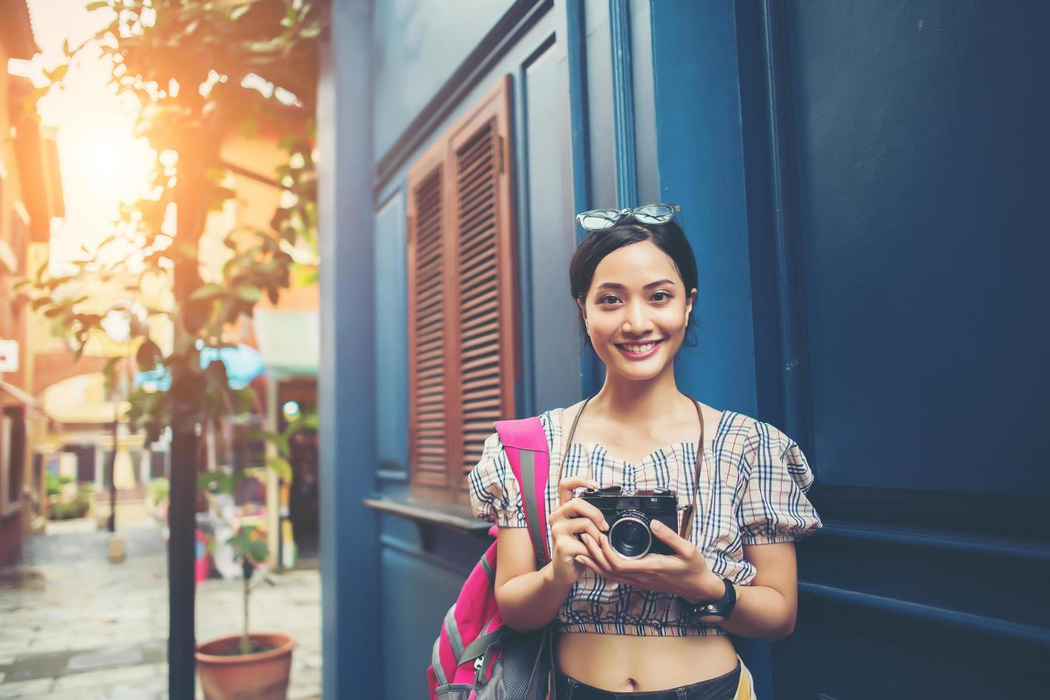 Portrait of pretty young hipster woman having fun in the city with camera photo