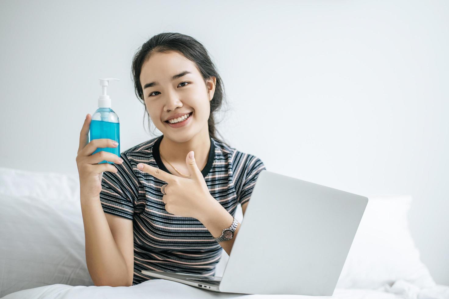 Young woman using hand washing gel photo