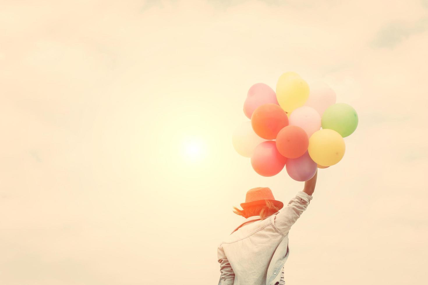 hermosa joven sosteniendo globos en la playa foto