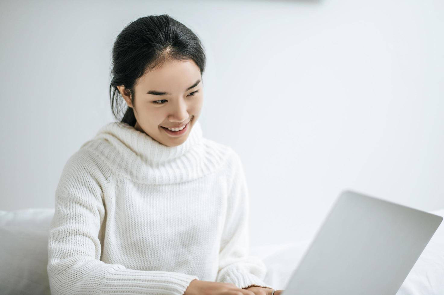 A young woman happily playing on her laptop photo
