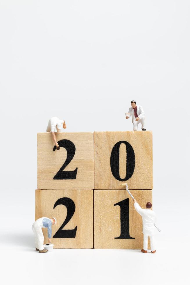 Figuras en miniatura de un equipo pintando bloques el número 2021 foto