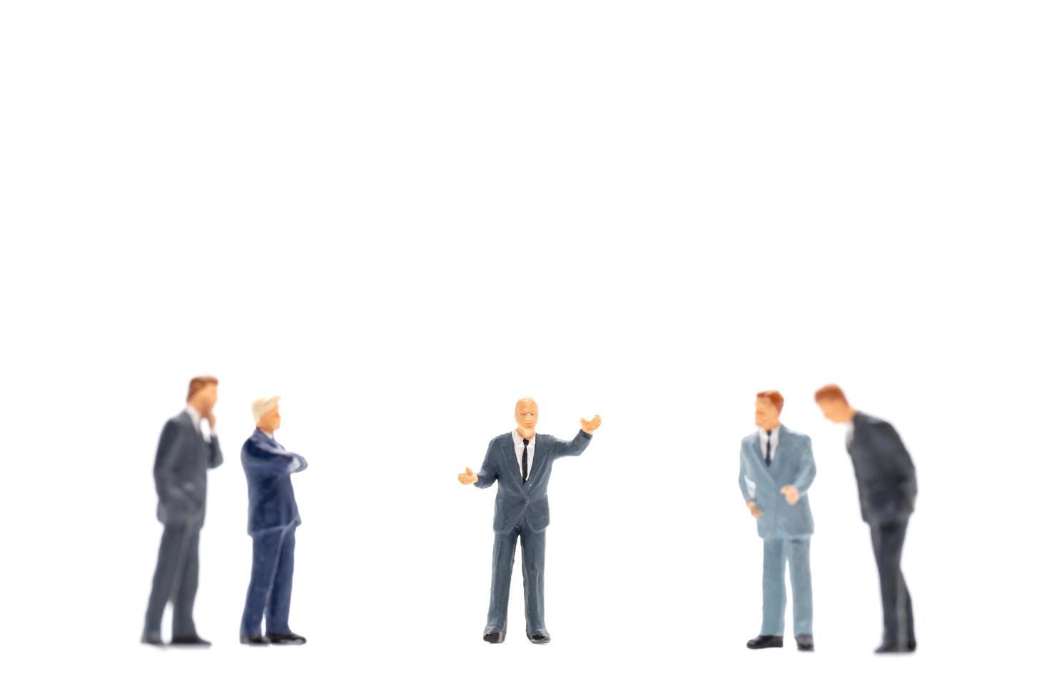 Figuras en miniatura de gente de negocios de pie sobre fondo blanco. foto