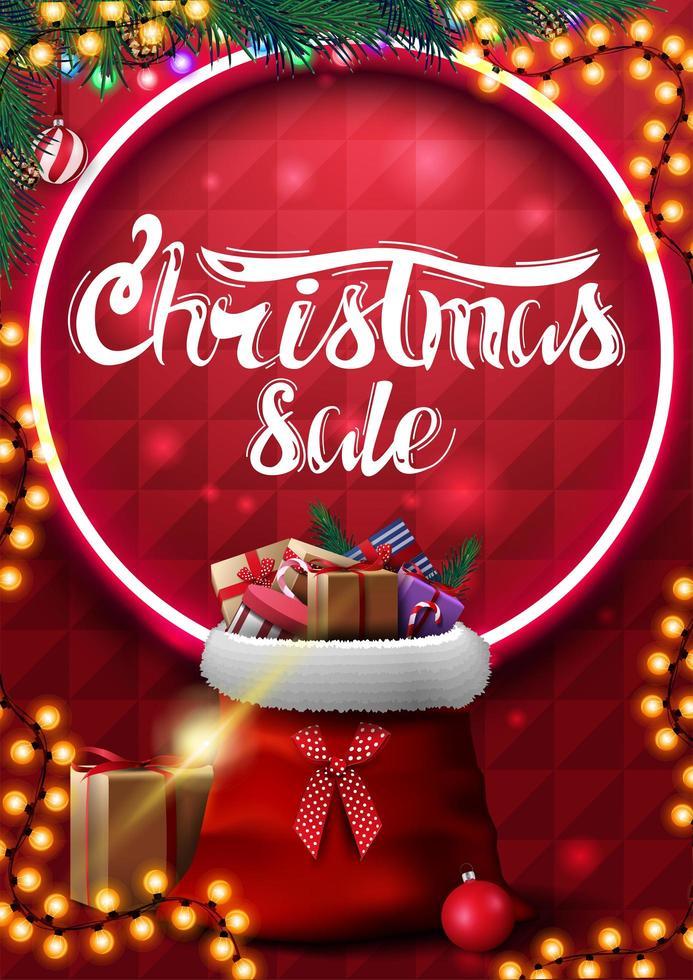 venta de navidad, banner vertical rojo con guirnalda, ramas de árboles de navidad, círculo de neón, letras hermosas y bolsa de santa claus con regalos vector