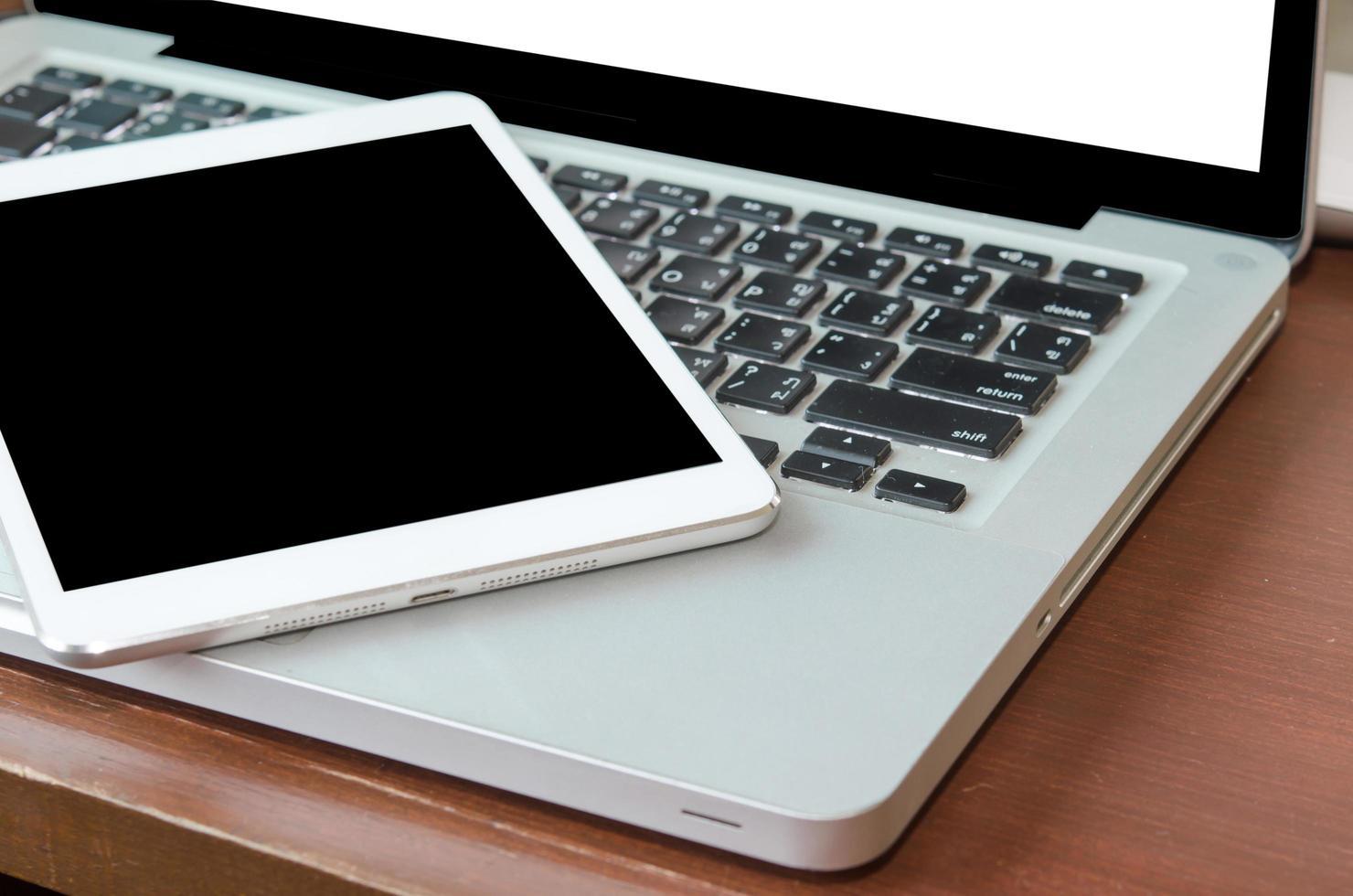 Blank screen tablet on laptop photo