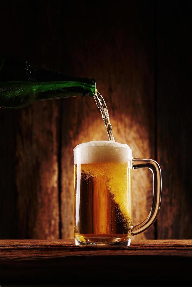 se vierte la cerveza en un vaso foto