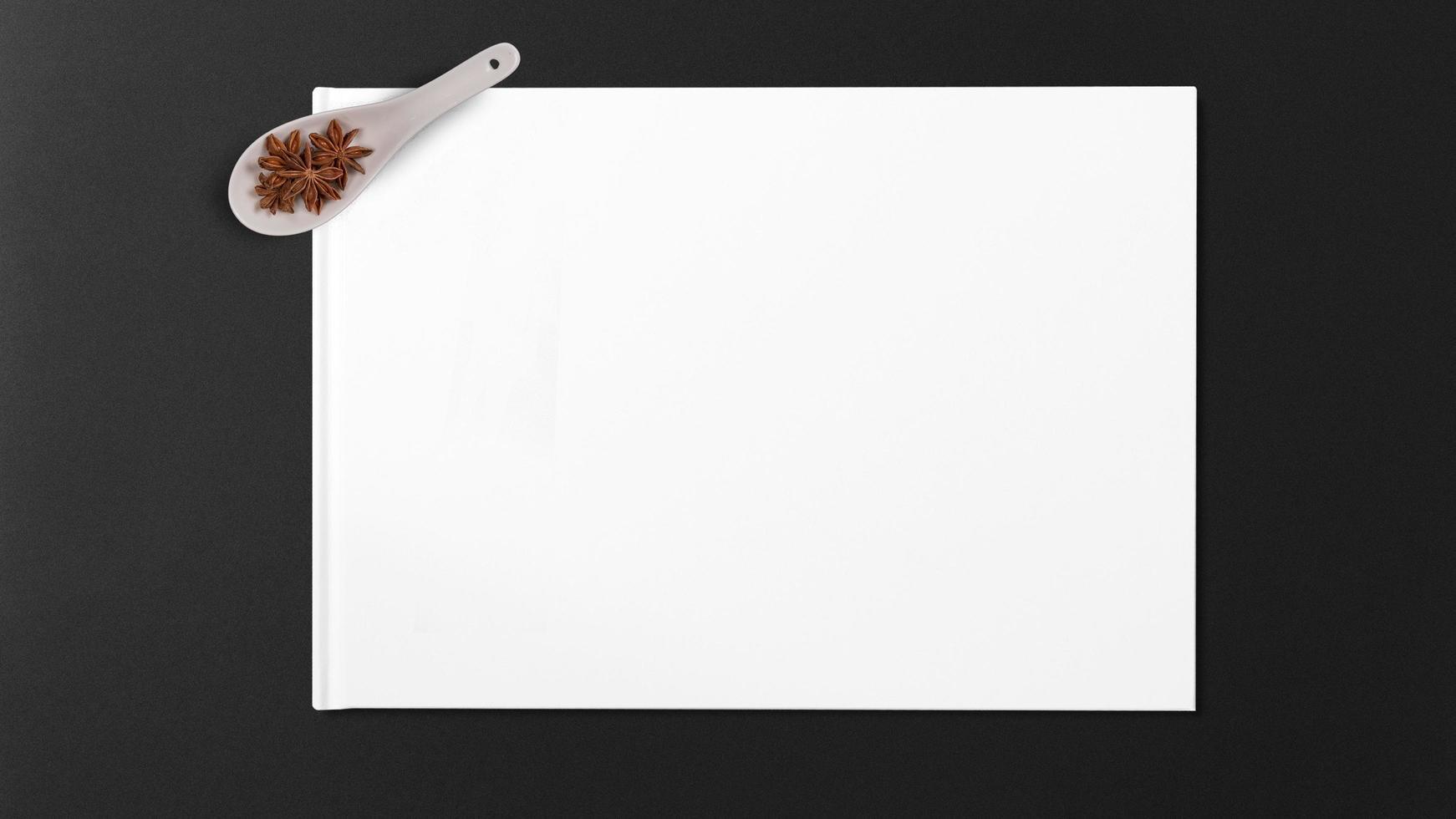 Anís estrellado en cuchara de madera sobre papel blanco sobre fondo negro foto