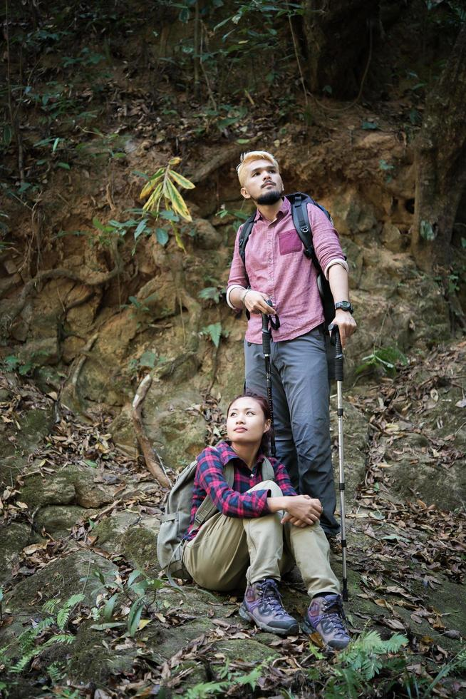 Young tourist couple hiking in forest photo