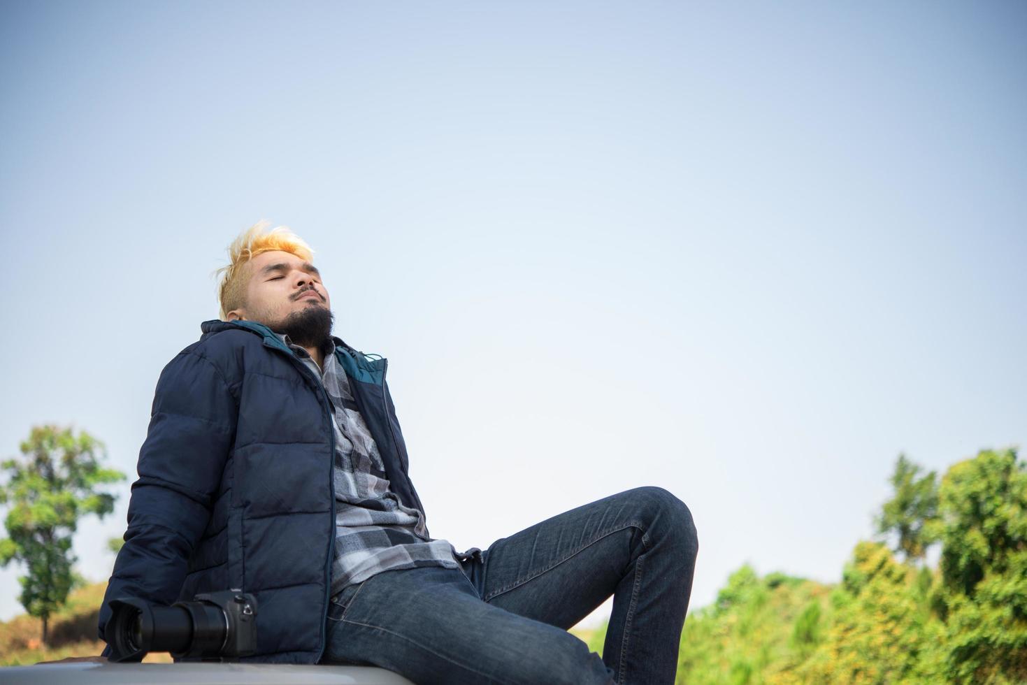 joven excursionista disfrutando de la naturaleza sentado en su camión foto