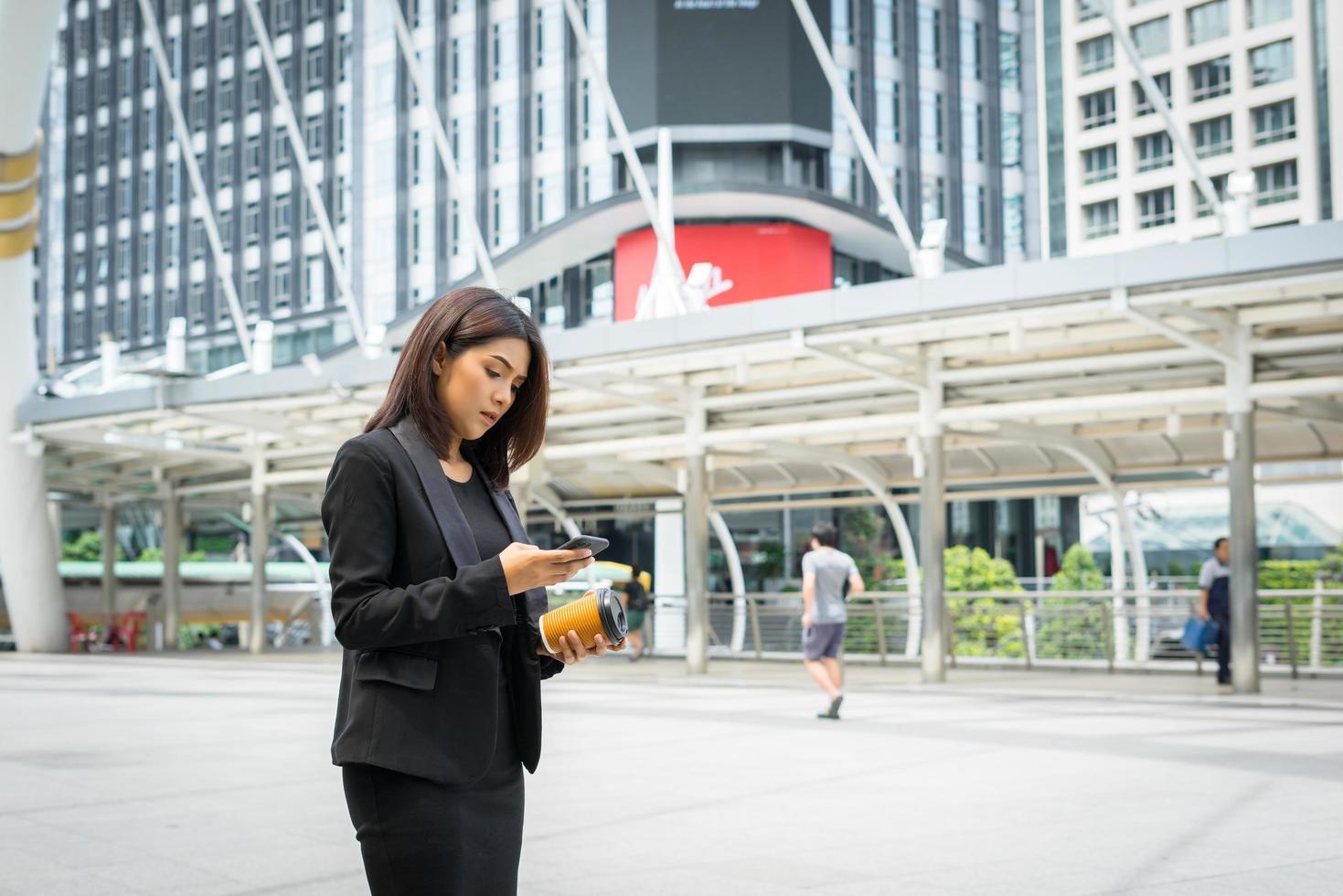 mujer de negocios, utilizar, teléfono, con, café, ambulante, en la calle foto